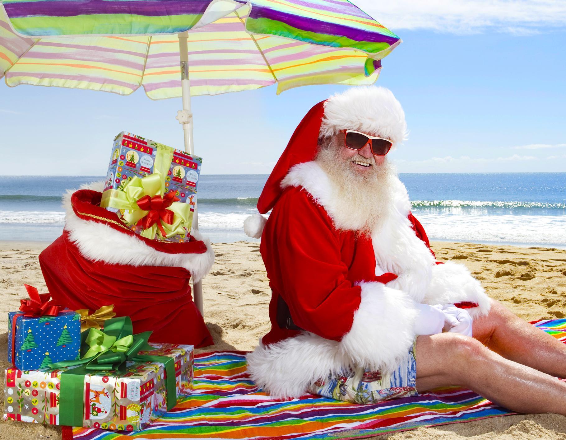 Joulupukki istuu rannalla lahjojen kanssa