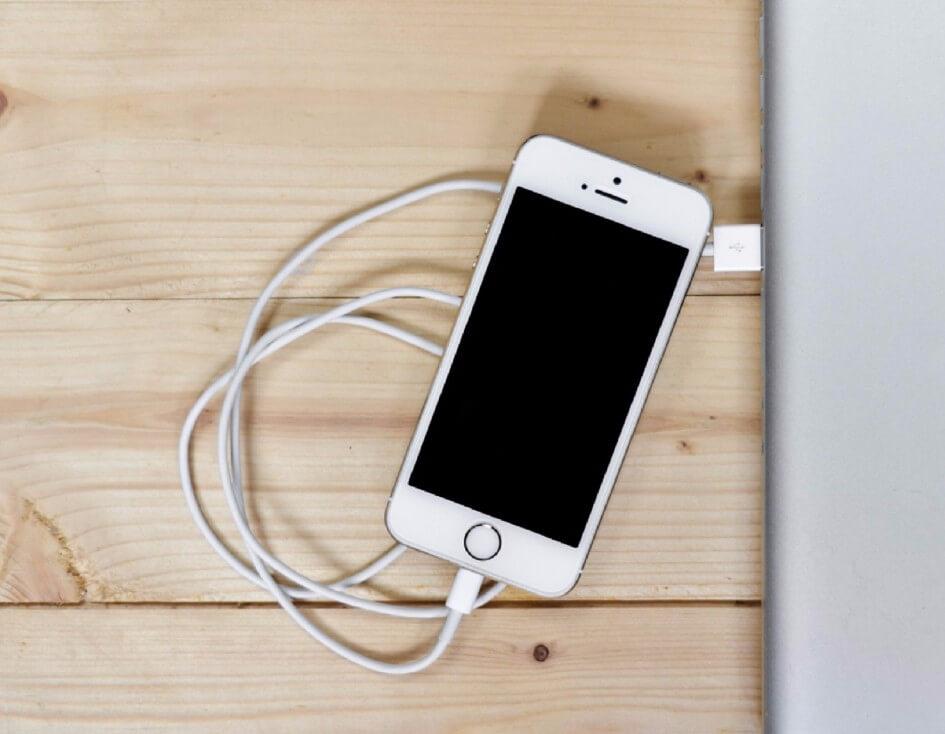 Iphone puhelin latautuu kannettavassa tietokoneessa puupöydällä