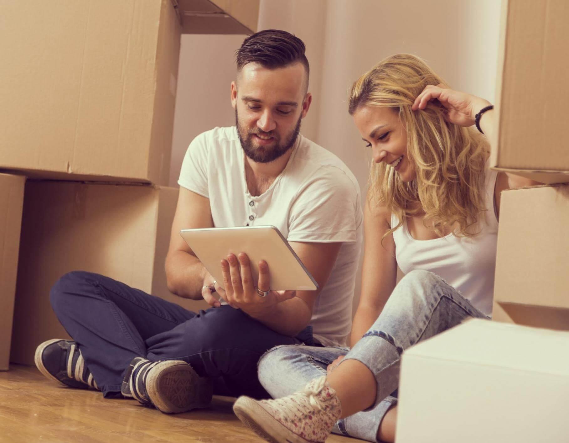 Nainen ja mies katsoo tablettia muuttolaatikoiden keskellä