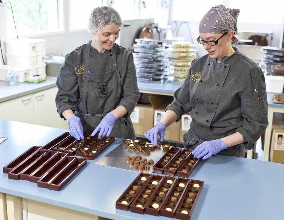 Suklaatilan työntekijöitä Suojärvellä laittaa suklaita paketteihin